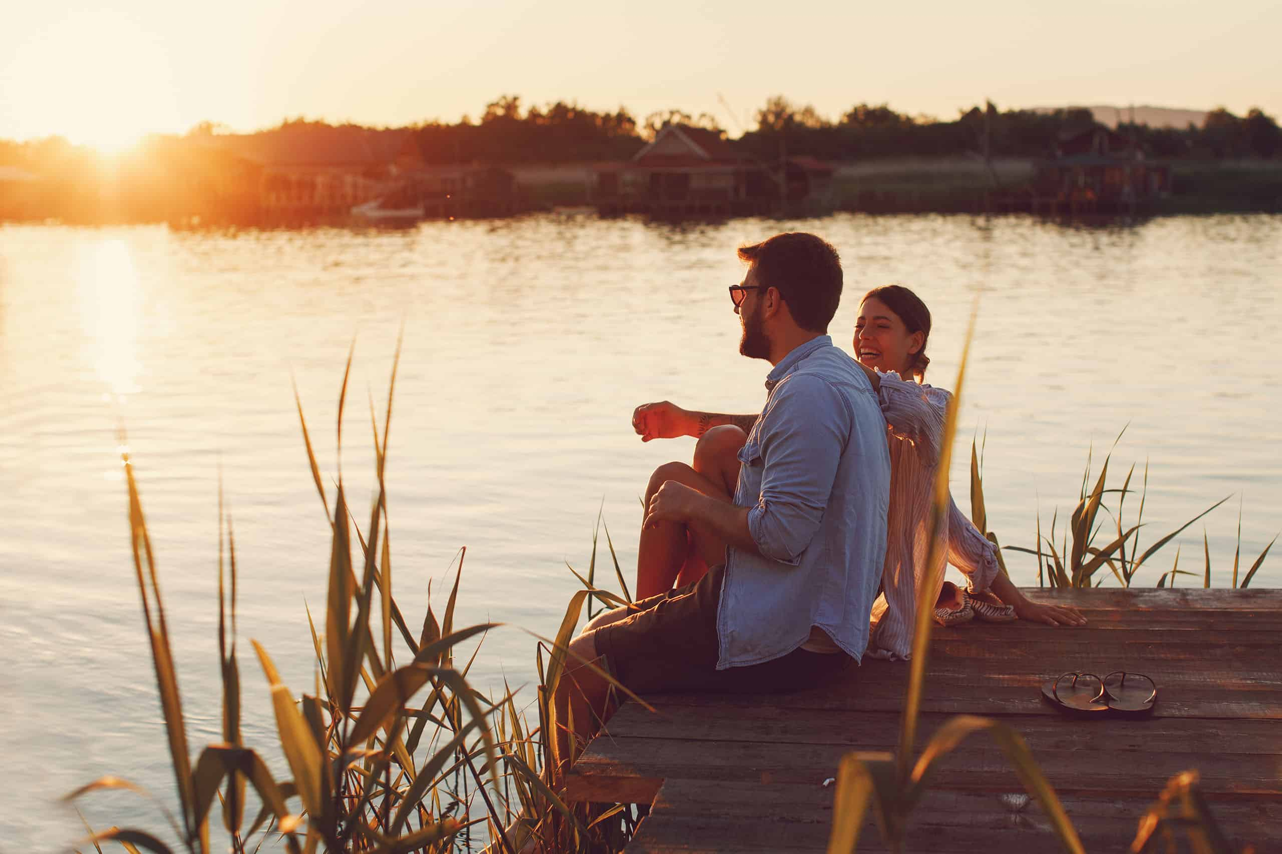 young-loving-couple-enjoys-by-the-river-during-the-sunset